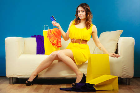consumerism: Shopping consumerism concept. Young woman with credit card buying sitting on sofa with paper bags and new clothes