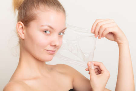 mujer maquillandose: Belleza cosm�ticos cuidado de la piel y el concepto de salud. Primer rostro de mujer joven, muchacha que quita facial mascarilla exfoliante en gris. Descamaci�n Foto de archivo