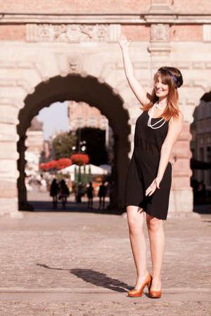 invitando: Chica de la aleta haciendo acogedora bienvenida gesto de la mano. Mujer de la vendimia de la moda retro estilo en vestido negro al aire libre en la calle del casco antiguo de Gdansk Danzig