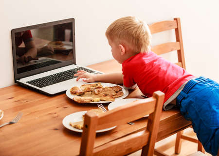bad boy: Children, technology and home concept  - little boy child eating meal while using laptop pc computer at home. Bad habits Stock Photo