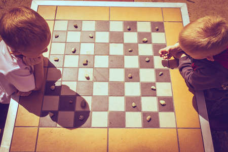 sibling rivalry: Draughts board game. Little boys clever children kids playing checkers thinking, outdoor in the park top view. Childhood and development