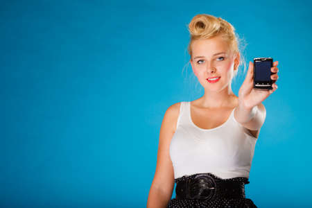 librarian: Librarian, accountant and secretary concept. Retro, pin up style. Young blonde woman holding smartphone on blue background in studio.