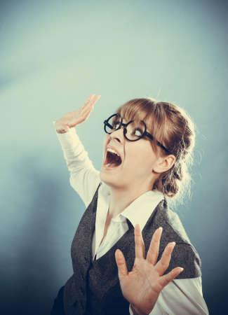 upward: Business woman screaming looking upward in full fear wide open mouth grey wall background.