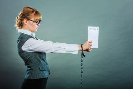 Business concept. Serious woman businesswoman with chained hands holding contract, side view grungy background photo
