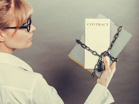 businesspersons: Business concept, limited by contract. Woman holding in hands paper document chained with padlock