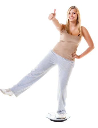 weightloss: Slim down concept. Woman plus size large content girl on weight scale celebrating weightloss progress after healthy dieting, thumb up gesture