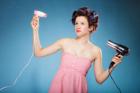 blow drier: Young woman preparing to party having fun, funny girl styling hair with two hairdreyers retro style on blue