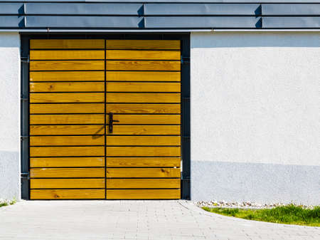 garage on house: Garage, house or warehouse entry. Yellow wooden door outside.