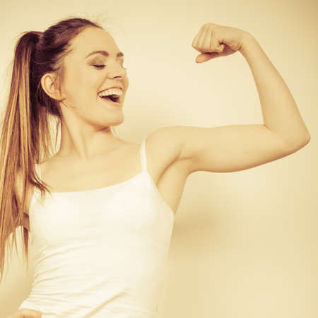 strong: Strong woman showing off muscles. Young happy girl smiling. Power and strength concept.