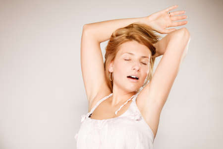 beautiful girl face: Attractive blonde woman with no make up yawning stretching waking up gray background
