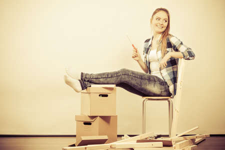 Woman moving into new apartment house assembling furniture with screwdriver. Young girl sitting on chair arranging interior and unpacking boxes.   photo