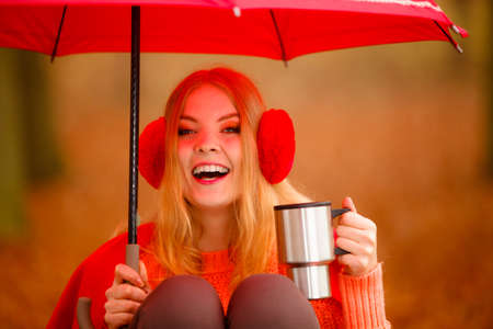 Happiness carefree and fall concept. Young woman in red relaxing in autumn park on bench under umbrella, enjoying hot drink holding mug with warm beverage. Orange leaves background photo