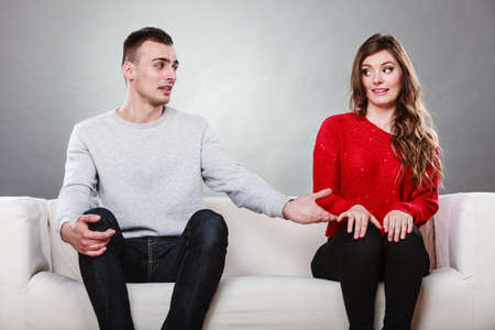 date: Shy woman and man sitting on sofa couch next each other. First date. Attractive girl and handsome guy meeting dating and trying to talk. Male offering a hand to female. Stock Photo