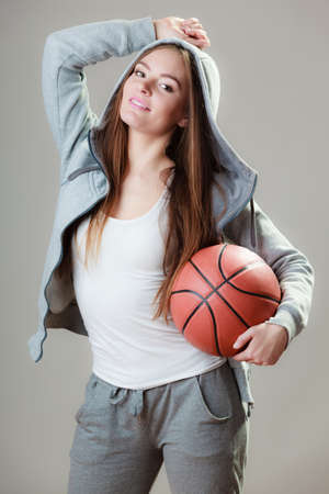 sportingly: Young sporty woman teen girl long hair holding basketball on gray background