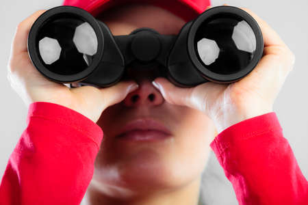 lifesaving: Accident prevention and water rescue. Closeup girl in red lifeguard outfit on duty looking through binocular on gray Stock Photo