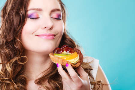 woman eating cake: Bakery sweet food and people concept. Content attractive woman closed eyes holds cake cupcake in hand smelling blue background