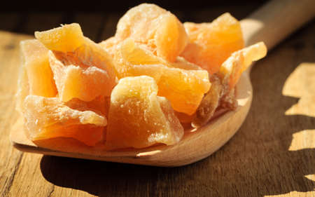 crystallized: Closeup candied crystallized ginger candy pieces on wooden spoon. Healthy food, home remedy for nausea motion sickness, colds. Stock Photo