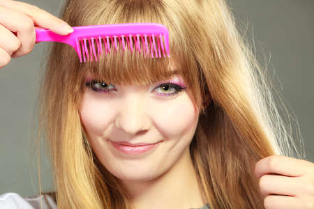 hairstyle woman: Fashion beauty and haircare concept. Closeup young woman refreshing her hairstyle she combing her hair fringe with pink comb