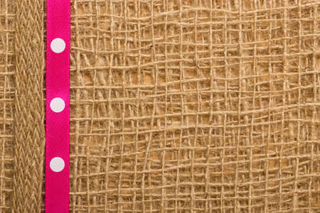 polka dotted: Polka dotted pink ribbon on brown mesh material, natural burlap