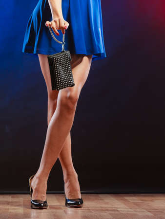 party outfit: Celebration disco and evening fashion concept - woman in blue dress holding handbag bag, dancing in the club, part of body female legs in high heels on party floor