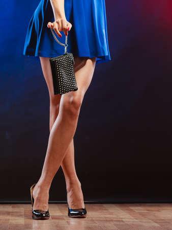 Celebración concepto de discoteca y noche de la moda - mujer en vestido azul de la celebración del bolso, bailando en el club, parte del cuerpo piernas femeninas en los zapatos de tacón alto en el piso de las partes