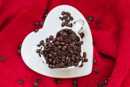 love pic: Coffee klatsch java concept. Heart shaped white cup filled with roasted coffee beans on red cloth