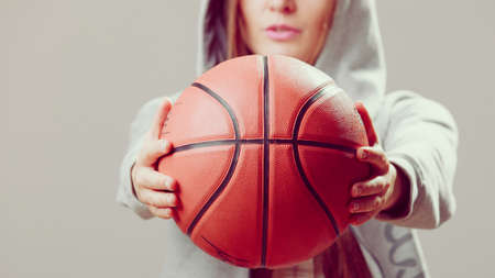 hooded sweatshirt: Sporty teenager girl wearing hooded sweatshirt holding basketball. Teen sport.