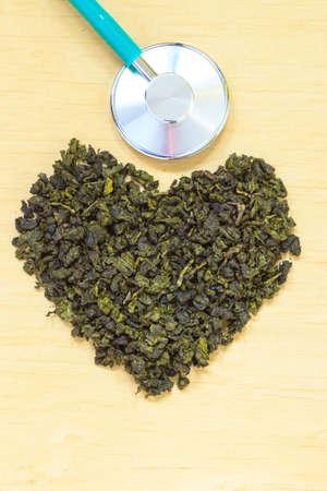 essen und trinken: Di�t-Gesundheitskonzept. Gr�ner Tee herzf�rmige Stethoskop auf h�lzerne Oberfl�che. Gesunde Ern�hrung Getr�nk f�r niedrigere Herz-Risiko