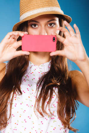 Technology internet and happy people concept - teen girl taking self picture selfie with smartphone camera, woman using cell phone on blue photo