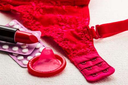 lace bra: Healthcare medicine, contraception and birth control. Closeup oral contraceptive pills, lipstick and condom with red lace bra lingerie. Stock Photo