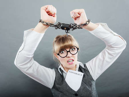 arrest: Crime, arrest jail or business concept. Angry unhappy emotional woman with chained hands on grunge background Stock Photo