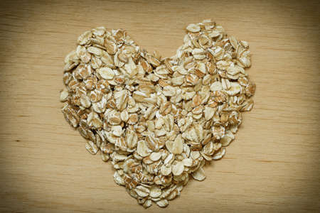 lowering: Dieting healthcare concept. Oat cereal heart shaped on wooden surface. Healthy food for lowering cholesterol, protect heart.