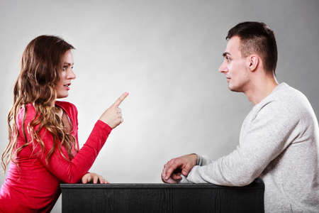 threatening: Couple talking on date. Woman warning man. Boyfriend and girlfriend having conversation. Girl threatening with finger. Stock Photo