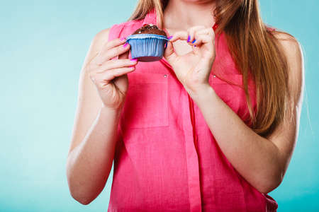 gluttony: Delicious tasty sweet chocolate muffin in human hands. Confectionery food. Gluttony concept.