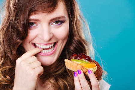 licking finger: Bakery, sweet food and people concept. Closeup smiling cute woman curly hair holding fruit cake cupcake in hand on blue Stock Photo