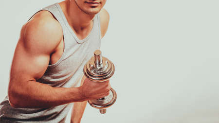 Bodybuilding. Strong fit man exercising with dumbbells. Closeup muscular young guy lifting weights gray backgroun