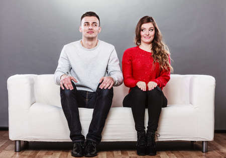 Shy woman and man sitting on sofa couch next each other. First date. Attractive girl and handsome guy meeting dating and trying to talk. Stock fotó