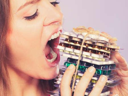 túladagolás: Nő vesz tablettát. Lány női étkezési halom tabletta. Drogfüggő és egészségügyi koncepciót. Overdose. Stock fotó