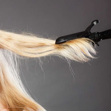 hairstyling: Hairstyling. Closeup blonde woman long haired making hairstyle hairdo with electric hair iron straightener gray background