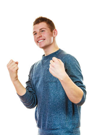 clenching: Success positive emotions. Happy young man successful lad with arms up clenching fist isolated on white background