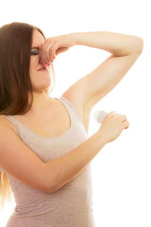 oler: Cuidado de la piel y la higiene diaria. Muchacha que aplica el desodorante en barra. Mujer joven que pone desodorante en las axilas, pellizca apesta axila nariz, muy mal olor en blanco Foto de archivo