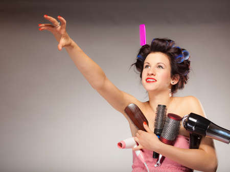 hair drier: Young woman preparing for date having fun, cute girl with curlers styling hair with many accessories comb brush hairdreyer on  gray