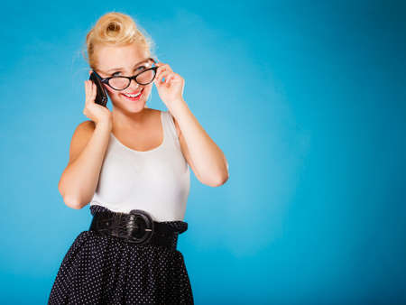 librarian: Librarian, accountant and secretary concept. Retro, pin up style. Young blonde woman in glasses. Girl holding smartphone on blue background in studio.