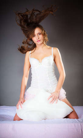 sensuality: Sensuality and beauty. Wind in hair. Attractive sexy woman with pillow on bed.