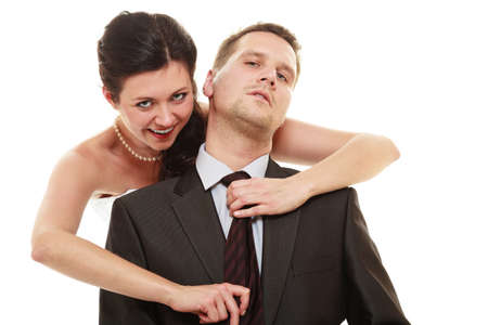 domination: Emancipation. Woman pulling tie of man, wife showing her domination over husband isolated on white. Stock Photo