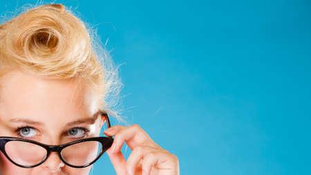 oculista: Optometrista, oculista y el concepto oftalmólogo. Mujer rubia joven con gafas en el fondo azul en el estudio. Foto de archivo