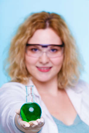 biochemist: Experiment, research in progress. Chemist woman or student girl, laboratory assistant or scientific researcher with chemical glassware test flask on blue