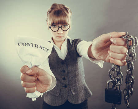 law breaking: Businesswoman woman ending agreement deal. Young girl holding chain breaking free creasing squeezing paper. Termination, breach of contract.