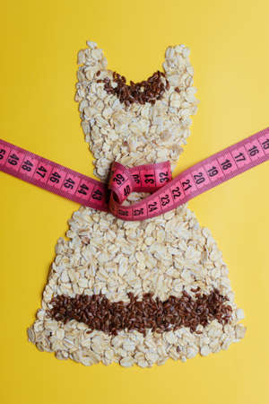 waist down: Dieting healthy eating slim down concept. Female dress shape made from oatmeal flax seeds with measuring tape around thin waist on yellow