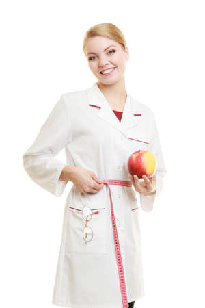 recommending: Slim down dieting concept. woman in white lab coat recommending healthy food. Doctor specialist dietitian holding fruit apple measuring her waist isolated. Stock Photo